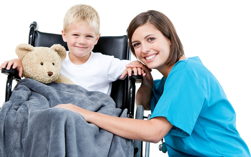 Nice female doctor carrying adorable little boy with his teddy bear in the wheelchair at the hospital