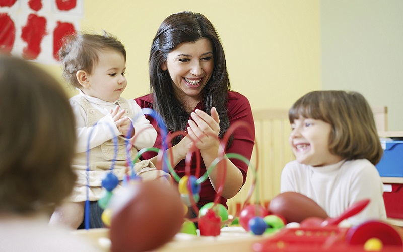 three little girls and female teacher in kindergarten