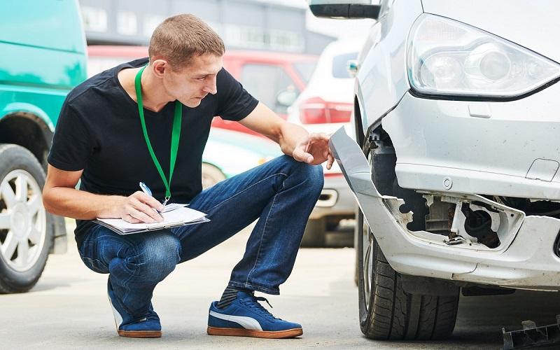 Insurance agent recording damage after car crash during inspecting damaged automobile on claim form